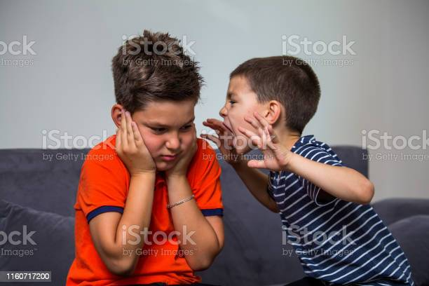 Quarreling Kids Boy Shouting At His Brother Child Shouting Loud Little Child Boy Holding Hands Near Head And Scares His Brother Stock Photo - Download Image Now