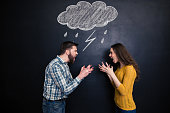 istock Quarrelling couple standing against background of chalkboard and screaming 508247980