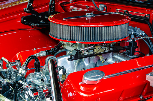 Quarter view of a streetrod engine with red air filter, valve covers and engine compartment