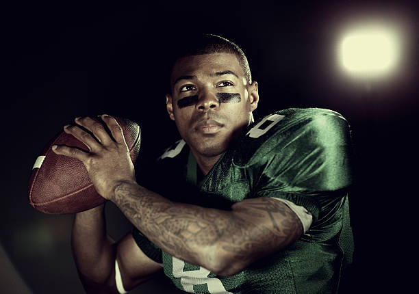 Quarterback Portrait of an African American tackle football player ready to throw downfield. quarterback stock pictures, royalty-free photos & images