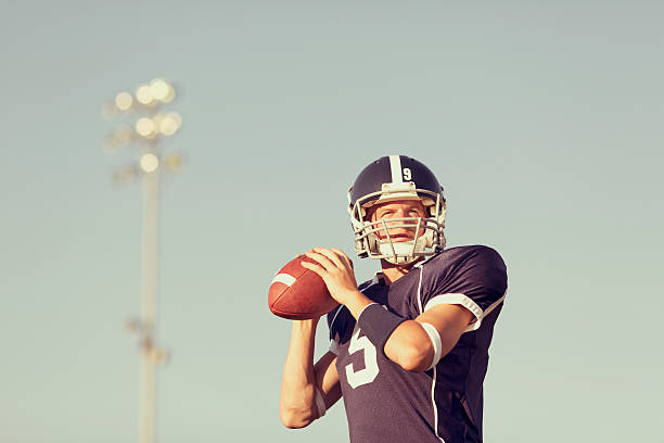 Quarterback An American Football quarterback goes for the touchdown pass. quarterback stock pictures, royalty-free photos & images