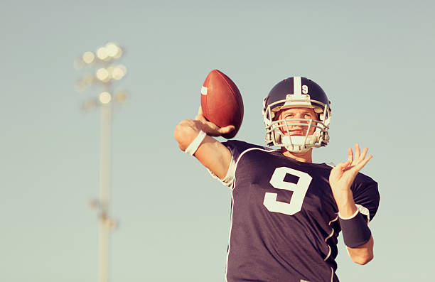 Quarterback An American football Quarterback passes the ball downfield. quarterback stock pictures, royalty-free photos & images