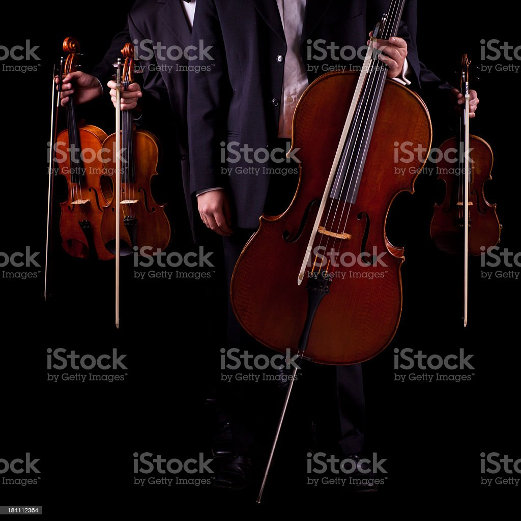 Quartet of string instrument musicians on a black background royalty-free stock photo