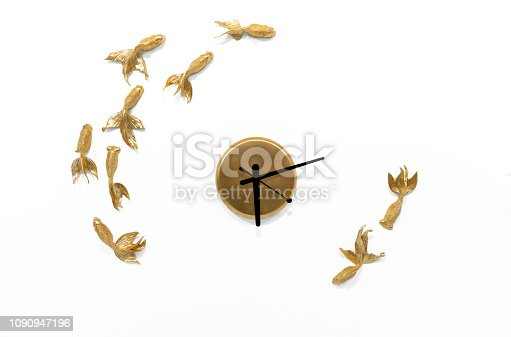 812823858istockphoto Quartz clock with goldfish on a white wall. 1090947196