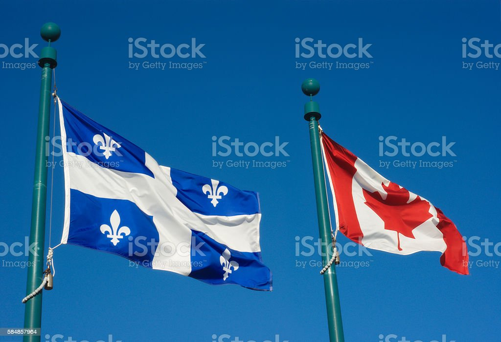 Quebec and Canada flags fluttering in the wind  blue sky stock photo