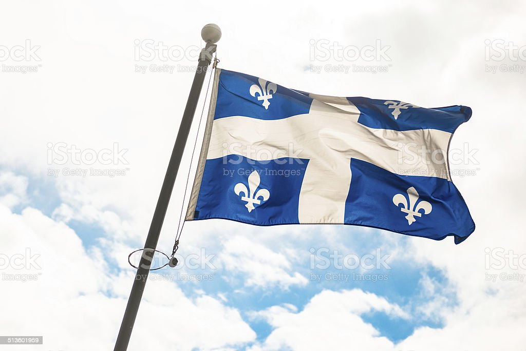 quebec flag waving on the sky stock photo