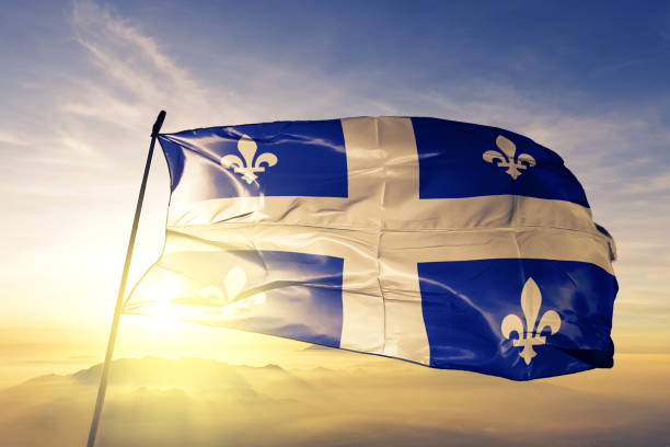 Quebec province of Canada flag textile cloth fabric waving on the top sunrise mist fog stock photo