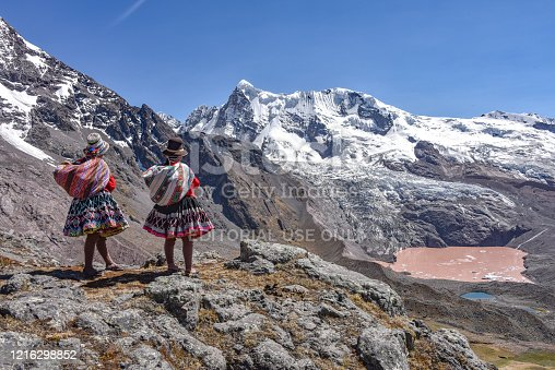 Quechua girls take in views across the snow-capped mountains and lakes of the Cordillera Vilcanota in the Peruvian Andes. Cusco, Peru