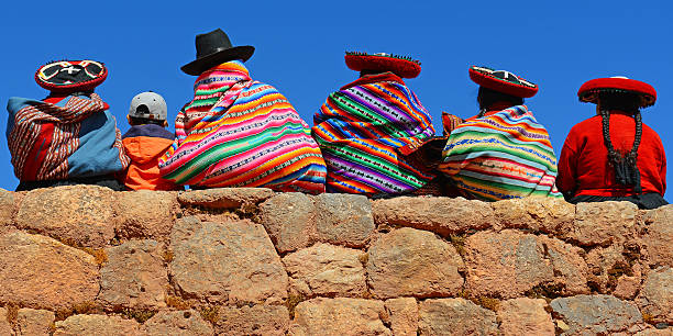 Quechua Indigenous Chincheros, Peru - June 23, 2013: Quechua ladies with colorful textiles and hats sitting on an ancient Inca Wall together with a young boy with modern clothing. peruvian culture stock pictures, royalty-free photos & images