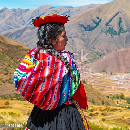 A Quechua indigenous woman looking over the Sacred Valley of the Inca in the archaeological site of Tipon, Andes mountain range, Cusco, Peru.