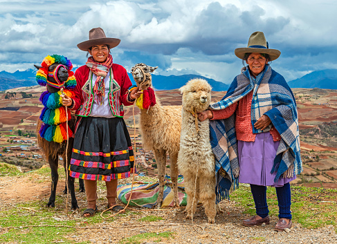A rural portrait of Quechua Indigenous Women in traditional clothes with their domestic animals, two llama and one alpaca, Sacred Valley of the Inca, Cusco, Peru.