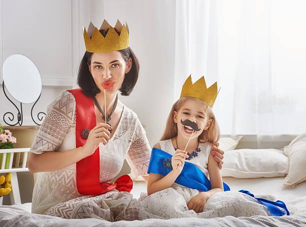 queen and princess in gold crowns - schnurrbart themenpartys stock-fotos und bilder