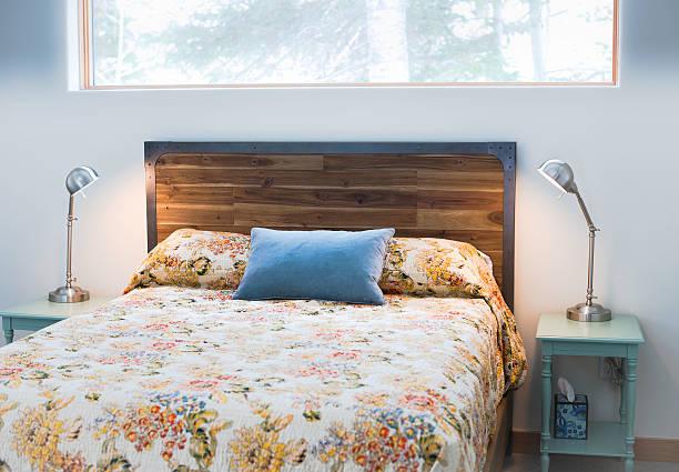 queen-size-bett mit tagesdecke mit blumenmuster und einem hölzernen kopfteil - cottage schlafzimmer stock-fotos und bilder