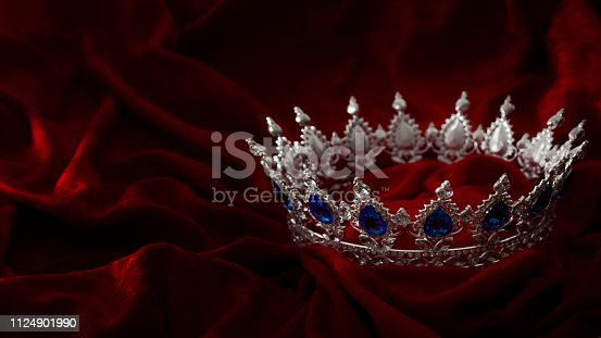 Queen coronation in fairy tales and legends monarchy and royal jewels concept with close up on a sparkling silver crown or tiara on low key dark red velvet background with copy space