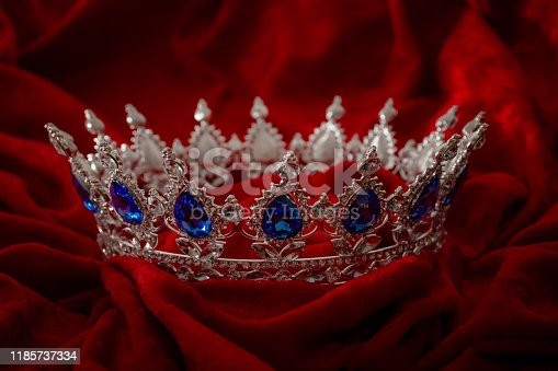 Queen coronation in fairy tales and legends monarchy and royal jewels concept with close up on a sparkling silver crown or tiara on low key dark red velvet background
