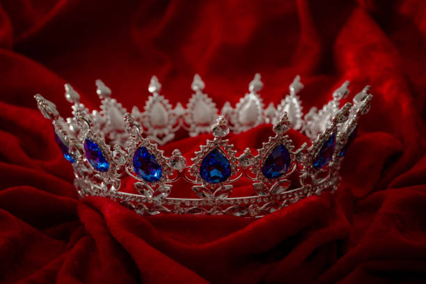 queen coronation in fairy tales and legends monarchy and royal jewels concept with close up on a sparkling silver crown or tiara on low key dark red velvet background - diadem stock pictures, royalty-free photos & images