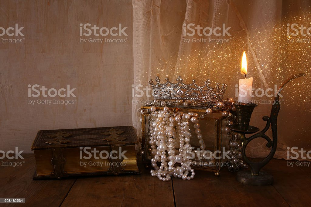 queen crown, white pearls next to old book stock photo