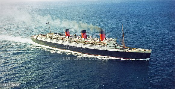 Long Beach, California, USA - December 19, 1967: Aerial view of the ocean liner RMS Queen Mary in the Pacific Ocean as she approaches Long Beach, California. The ship was retired and permanently moored in Long Beach where it still serves as a hotel, restuarants, museum and tourist attraction. Scanned film.