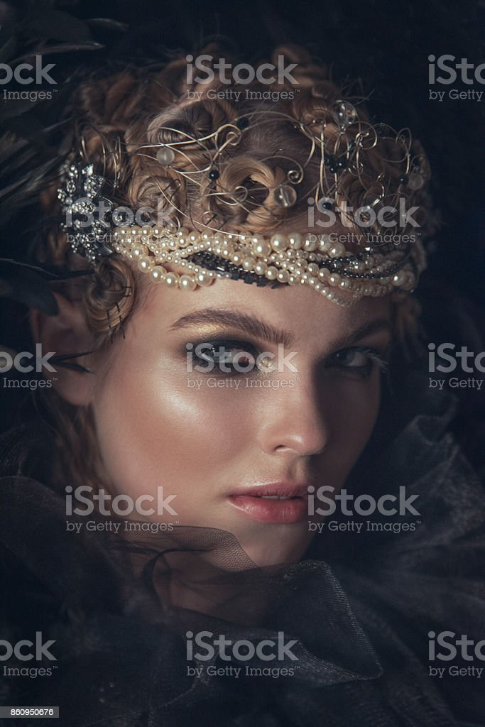 Queen of darkness in black fantasy costume on dark gothic background. High fashion beauty model with dark makeup. stock photo
