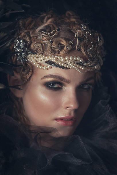 königin der finsternis in schwarz fantasy-kostüm auf dunklen gotischen hintergrund. mode schönheit mit dunklen make-up modell. - gothic kleid stock-fotos und bilder
