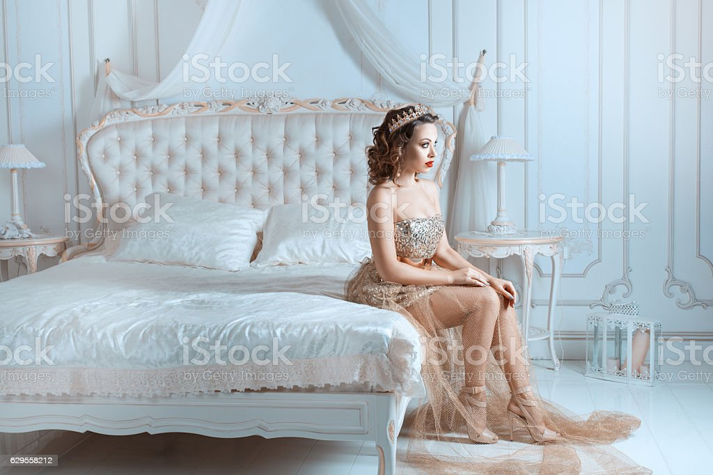 Queen sitting on the bed. stock photo