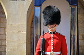 Windsor, England, United Kingdom, August 6, 2018 : A Royal Guard in his iconic uniform outside Windsor Castle Gate.