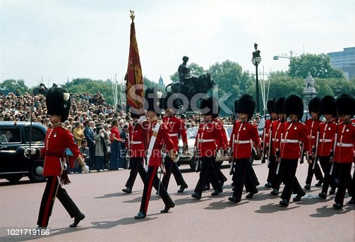London, England, UK, 1973. Changing of the Guards. Members of the Queens Guard regiment marching in front of Buckingham Palace. Furthermore: spectators.