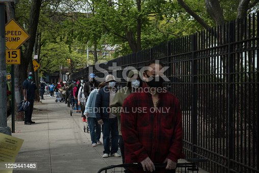 A large crowd of people wait in line outside a food pantry at St. Bartholomew's Roman Catholic Church in Elmhurst, Queens. Catholic charities have played a crucial role during the pandemic, handling a surge in food demand. The Elmhurst neighborhood is one of the hardest hit areas in Queens and has been called