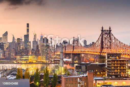 New York, New York, USA Manhattan skyline with the Queensboro Bridge at dusk from Queens.