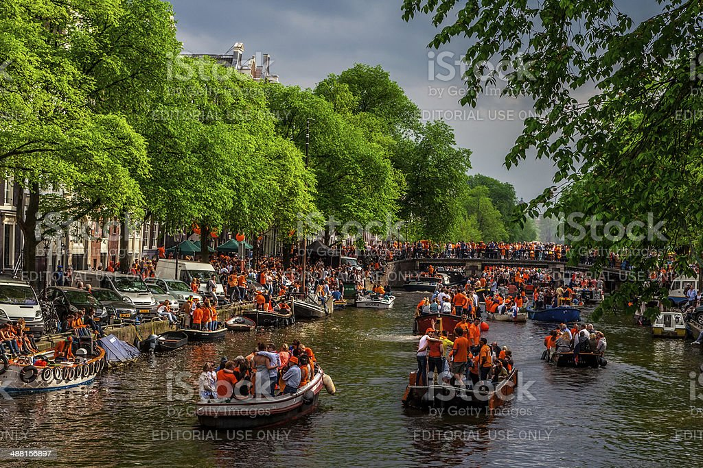 Queensday in Amsterdam Amsterdam, The Netherlands - April 26, 2014: Large crowds of people navigate through and walk along the canal in Amsterdam on Queensday Amsterdam Stock Photo