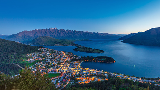 Beautiful Twilight Panorama of Queenstown. View down to the illuminated famous city of Queenstown in the south-west of the south island of New Zealand at Twilight - Night. Queenstown, Otago, South Island, New Zealand, Oceania