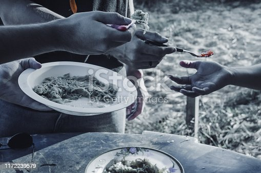 Hand holding plate with food and other hands holding fork with food being directed to the receiving hand and slightly blurred