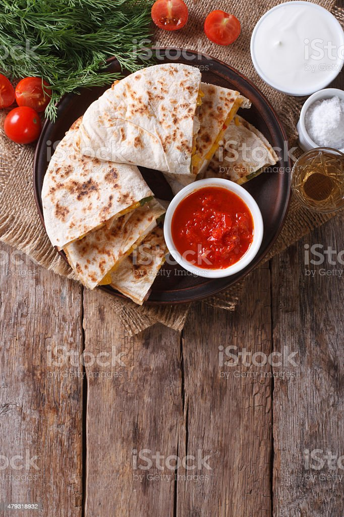 Quesadilla sliced and sauces on a plate. vertical top view stock photo