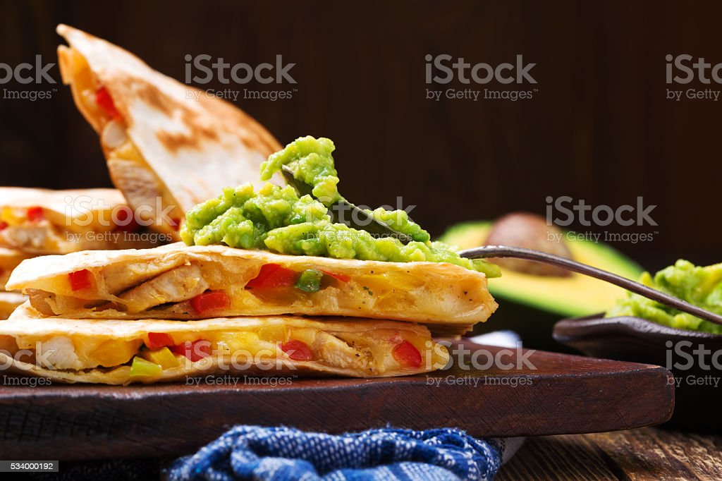 Quesadilla with chicken, served with guacamole or salsa sauce. stock photo