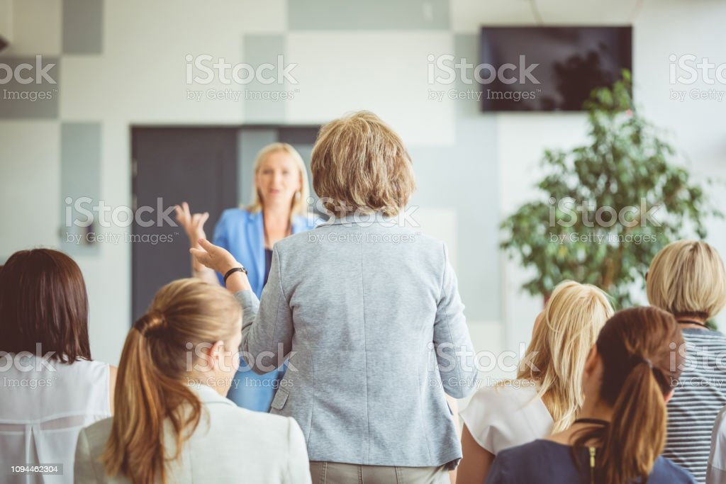 Question and answer session during seminar Rear view shot of a woman asking a question to presenter during a seminar. Group of business women a lecture. Adult Stock Photo