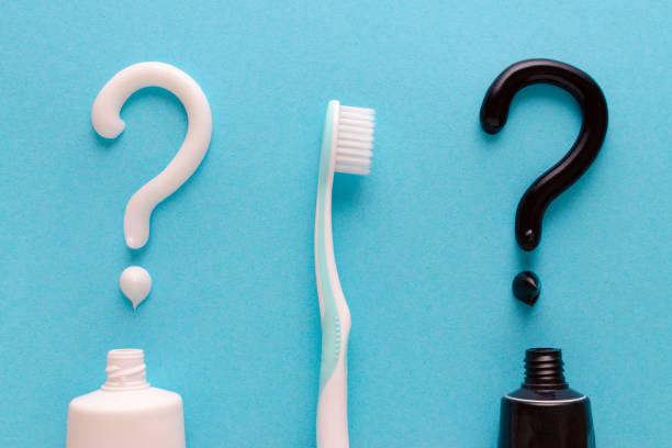 Frage aus weißer und schwarzer Zahnpasta, Zahnpflege, Zahnbürste auf blauem Hintergrund – Foto