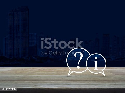 istock Question mark and information chat icon on wooden table over modern office city tower background, Customer support concept 849202794