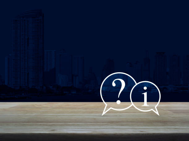 Question mark and information chat icon on wooden table over modern office city tower background, Customer support concept stock photo