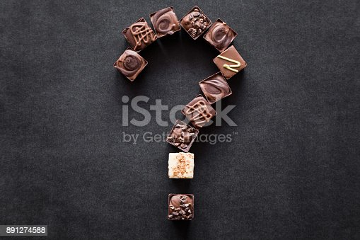istock Question mark created from pieces of chocolate candies on the dark table. Choice of the best sort and quality. Dieting questions and worries concept about sweet food. Tasty temptation. 891274588