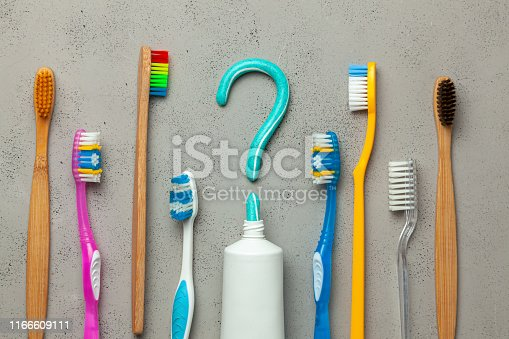 istock Question mark from toothpaste. The concept of choosing good toothpaste for teeth whitening. Tube of colored toothpaste and  toothbrush on  Gray background. Copy space for text 1166609111