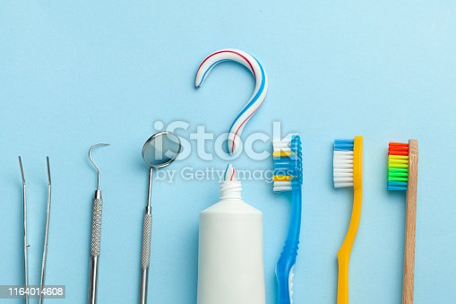 istock Question mark from toothpaste. Tube of colored toothpaste and  toothbrush and dentist tools, mirror, hook on blue background. The concept of choosing good toothpaste for brushing your teeth 1164014608