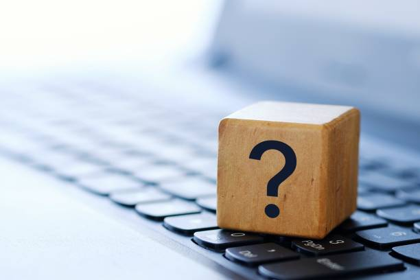 A question mark on a wooden cube on a computer keyboard, with a blurred background and shallow depth of field. stock photo