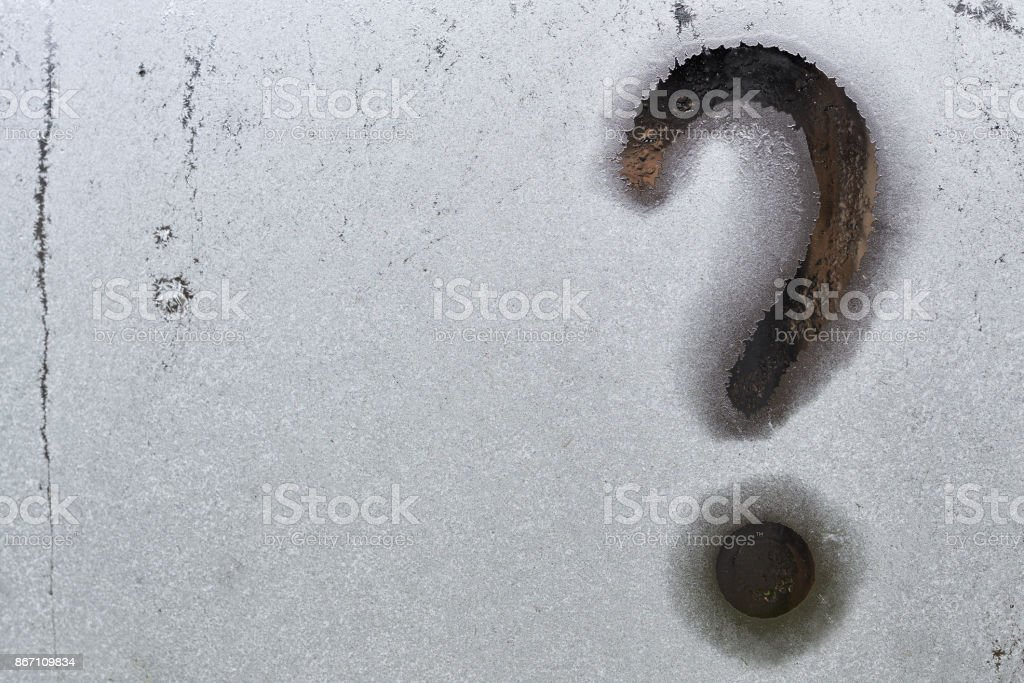 Question mark on frosty patterns on a glass winter background stock photo