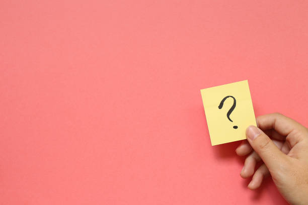 Question mark on memo paper on pink background. Solution concept stock photo