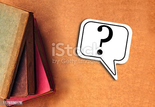 istock Question Mark Speech Bubble with old books on table 1179336178