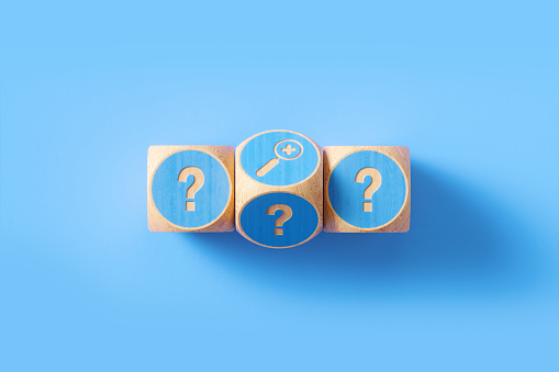 Question mark written blue wood blocks sitting over blue background. Horizontal composition with copy space. Q and A concept.