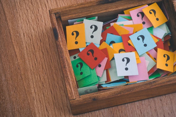 Question marks in a wooden box stock photo