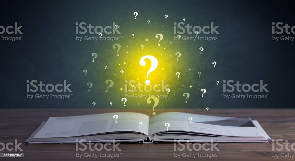 Question marks over book - foto stock