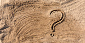 istock question marks written on beach sand close up, with copy space 1142202088