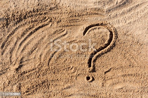 istock question marks written on beach sand close up, with copy space 1147309865